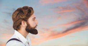 Boczny widok patrzeje daleko od przeciw chmurnemu niebu męski modniś Zdjęcia Stock