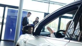 Boczny widok patrzeje oddalony i uśmiechnięty piękna dziewczynka podczas gdy siedzący w nowym samochodzie w motorowym przedstawie zdjęcie wideo