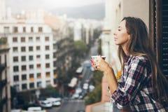 Boczny widok patrzeje szczęśliwy, uśmiecha się filiżankę apetyczna kawa i pije rozochocona młoda dziewczyna Zdjęcia Stock