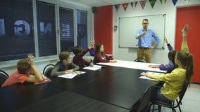 Boczny widok patrzeje uczni siedzi w sala lekcyjnej męski nauczyciel zbiory wideo