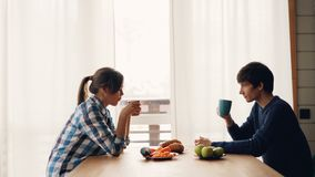 Boczny widok pić herbaciany przy stołem w kuchni wpólnie cieszy się pokojowego ranek przy i opowiadać siedzieć mężczyzny i kobiet zdjęcie wideo