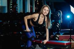 Boczny widok piękny sprawności fizycznej kobiety trening z ciężarami nad ćwiczenie ławką przy gym fotografia royalty free