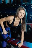 Boczny widok piękny sprawności fizycznej kobiety trening z ciężarami nad ćwiczenie ławką przy gym fotografia stock