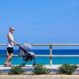 Boczny widok potomstwa ojcuje dosunięcie wózka spacerowego na plaży zdjęcia royalty free