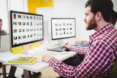 Boczny widok pracuje na fotografiach przy kreatywnie biurem redaktor Fotografia Royalty Free