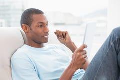 Boczny widok przypadkowy Afro mężczyzna używa cyfrową pastylkę na kanapie Obraz Royalty Free