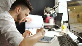 Boczny widok przypadkowy męski fotografia redaktor używa grafiki pastylkę w jaskrawym biurze 20s 4k zbiory