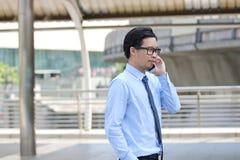 Boczny widok przystojny młody Azjatycki biznesowy mężczyzna opowiada na telefonie przy miastowym budynku miasta tłem zdjęcie stock