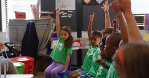 Boczny widok ras schoolkids podnosi ich ręki w sali lekcyjnej 4k zbiory
