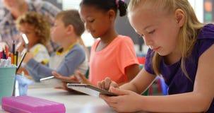 Boczny widok ras schoolkids studiuje na cyfrowej pastylce w sali lekcyjnej 4k zbiory