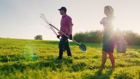 Boczny widok: Rodzina rolnicy z małym synem iść wpólnie zasadzać drzewa Znosi jabłoni rozsady, łopata i zbiory wideo