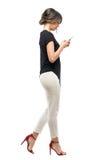 Boczny widok ruchliwie biznesowa kobieta w formalnym kostiumu odprowadzeniu, pisać na maszynie na telefonie komórkowym i Zdjęcie Stock