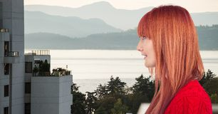 Boczny widok rudzielec kobieta z budynkiem i jeziorem w tle Fotografia Royalty Free