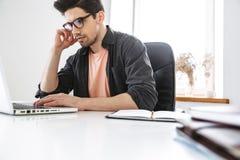 Boczny widok skoncentrowany mężczyzna w eyeglasses używać laptop fotografia stock
