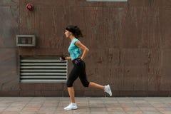 Boczny widok sporty młoda kobieta bieg na chodniczku zdjęcie stock