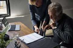 Boczny widok starsza osoba mężczyzna obsiadanie na wózku inwalidzkim patrzeje ubezpieczenie na życie kontrakta formę zdjęcie royalty free