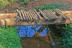 BOCZNY widok SUROWY FOOTBRIDGE NAD wodą Zdjęcia Stock