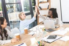 boczny widok szczęśliwi wielokulturowi bizneswomany daje wysokości pięć przy miejscem pracy obraz royalty free