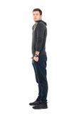 Boczny widok trwanie młody człowiek patrzeje kamerę w sportswear z rękami w kieszeniach Fotografia Stock