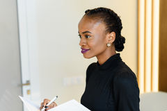 Boczny widok uśmiechać się pięknej biznesowej kobiety trzyma białego pióro w lekkim biurze i notepad z jaskrawymi fiołkowymi warg Obraz Stock