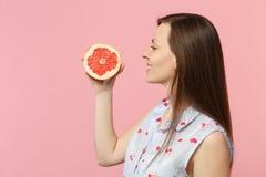 Boczny widok uśmiechnięta młoda kobieta w lata odzieżowym mieniu w ręki połówce świeży dojrzały grapefruitowy odosobniony na różo fotografia royalty free