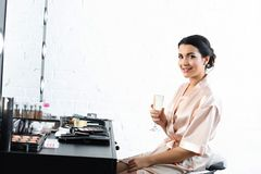 boczny widok uśmiechnięta panna młoda w jedwabniczym bathrobe i przesłona z szkłem szampański obsiadanie przy tabletop zdjęcia royalty free
