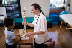 Boczny widok uśmiechnięty żeński terapeuta wyjaśnia chłopiec z sztucznym kręgosłupem obraz stock