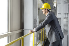 Boczny widok uśmiechnięty męski architekt opiera na poręczu w przemysle Zdjęcia Stock