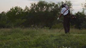 Boczny widok utrzymuje elektrycznej drobiażdżarki i rozcięcia trawy mężczyzna zbiory
