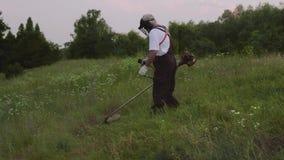 Boczny widok utrzymuje elektrycznej drobiażdżarki i rozcięcia trawy mężczyzna zbiory wideo