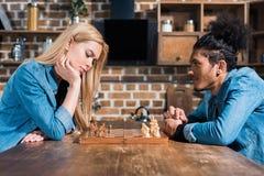 boczny widok wieloetniczni potomstwa dobiera się bawić się szachy wpólnie obraz royalty free