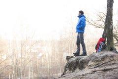 Boczny widok wycieczkowicz pozycja na krawędzi faleza w lesie Zdjęcie Royalty Free