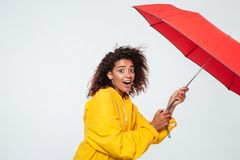 Boczny widok zdziwiona afrykańska kobieta w deszczowa mienia parasolu Obraz Royalty Free