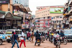Busy intersection, downtowm Kampala, Uganda. Boda boda motorcycle taxis and traffic on the intersection of Luwum Street and Burton Street, with shopping malls Stock Photography