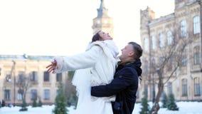 Boda del invierno pares del recién casado en vestidos de boda el novio detiene a la novia en sus brazos, haciendo girar son felic metrajes