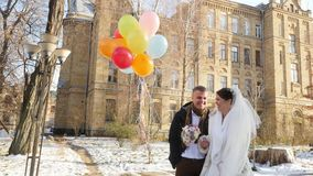 Boda del invierno, recienes casados felices, de risas con los globos brillantes, multicolores día nevoso soleado, la arquitectura metrajes