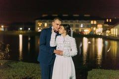 Boda romántica Novia y novio que abrazan cerca del lago de la noche iluminado con la luz ámbar brillante del pasillo del banquete Imagen de archivo