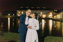 Boda romántica Novia y novio que presentan cerca del lago de la noche iluminado con la luz ámbar brillante de ventanas del pasill Imagenes de archivo