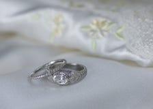 Boda y anillos de compromiso en el satén Foto de archivo
