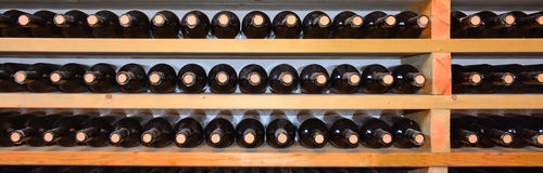 Bodega con las botellas en estantes de madera Foto de archivo
