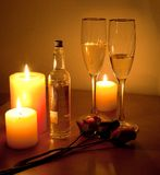 LOVE. Bodegon about love and a romantic evening. A few glasses of champagne, roses, candles and massage oil Royalty Free Stock Image