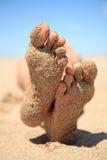 Bodem van voeten die met zand worden behandeld stock fotografie