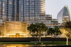 Boden-Boden von Burj Khalifa mit Beleuchtung, Bäumen und, Gebäuden am Abend, Dubai Lizenzfreie Stockbilder