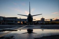 Bodenabfertigung eines Passagierflugzeuges geparkt zu einer Jet-Brücke mit Reflexion in einer Pfütze stockfoto