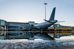 Bodenabfertigung eines Passagierflugzeuges geparkt zu einer Jet-Brücke mit Reflexion in einer Pfütze lizenzfreies stockfoto