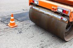 Bodenverdichter und Verkehrskegel auf dem Straßenbau Stockfoto