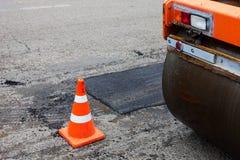 Bodenverdichter und Verkehrskegel auf dem Straßenbau Stockbild