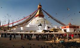 Bodhnath stupa med turister, buddistiska munkar och duvor Royaltyfri Foto