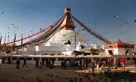 Bodhnath stupa with tourists, buddhist monks and pigeons Royalty Free Stock Photo