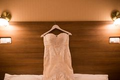The bodice of a weeding dress on a hanger in the hotel room. Stock Image
